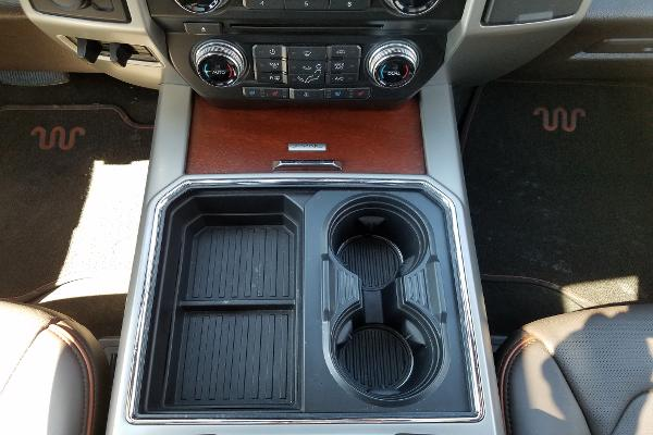 Novel addition here. You can change the number of center console cupholders from two to four or four to two with a sliding section. Storage exists underneath, too.