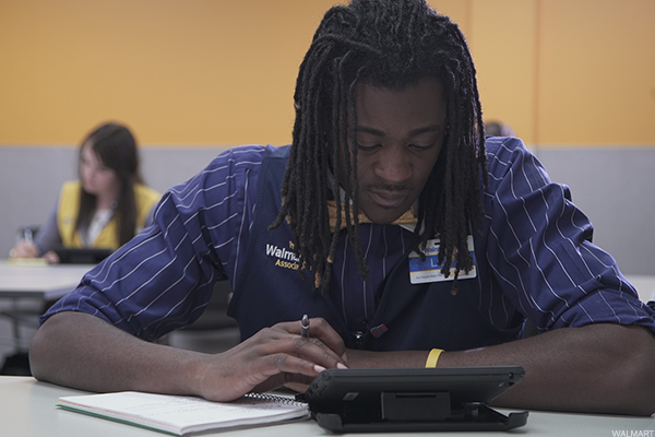 A Walmart employee in training using an iPad.